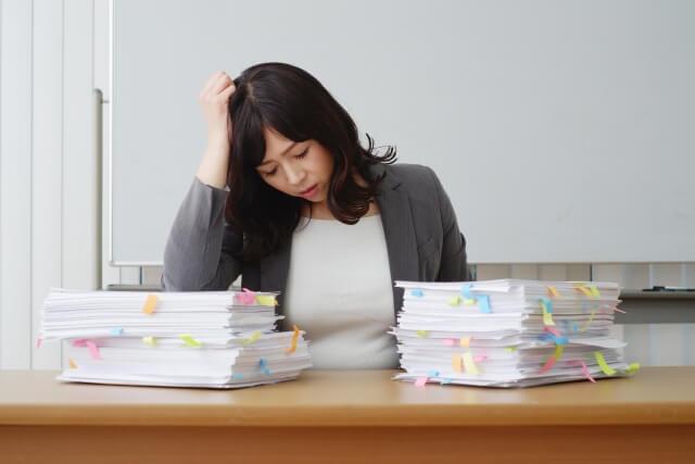 たくさんの文書処理に困っている女性